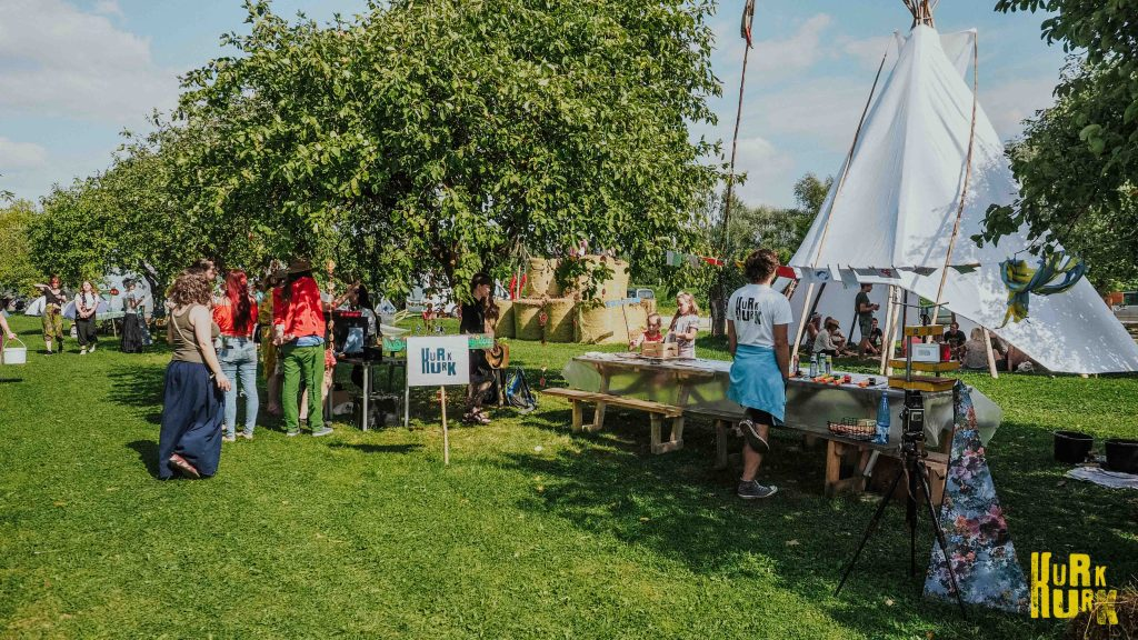 kūrybinės dirbtuvės festivalyje, iš kairės matomos obelys, po jomis įsikūrusios AFD dirbtuvės, o šalia, prie didelio stalo įsikūrusios Kurk Kurk dirbtuvės.