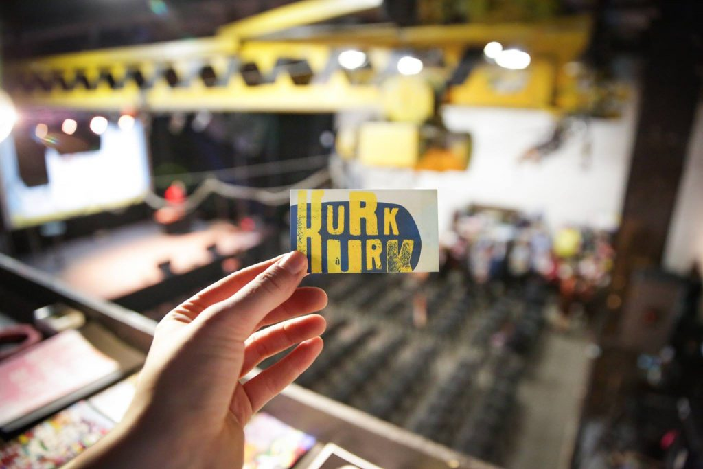 nuotraukoje matoma ranka laikanti vizitinę kortelę su Kurk Kurk logotipu, fonas išsiliejęs ir šiek tiek matoma salė.